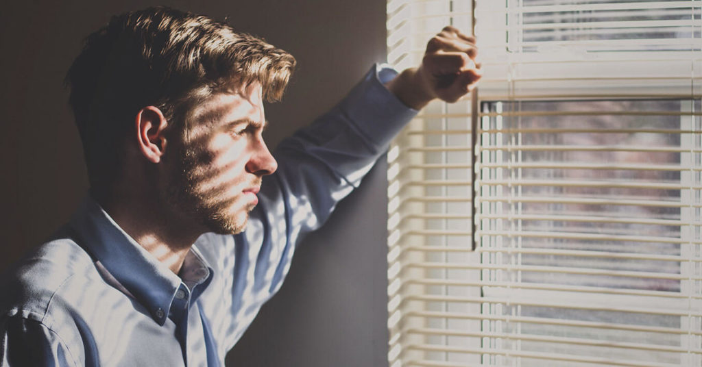 Man looking through window venetian blinds