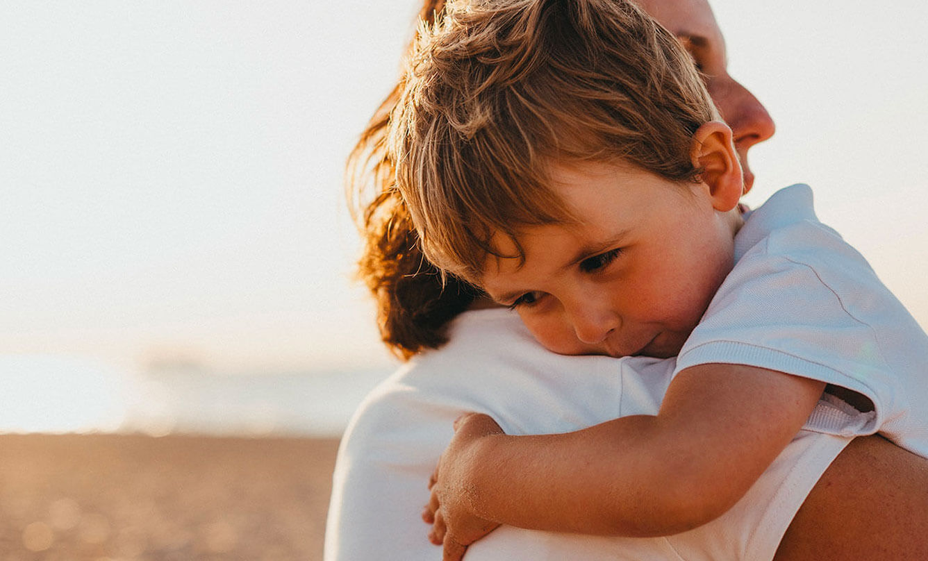 Child in arms of a parent on the beach